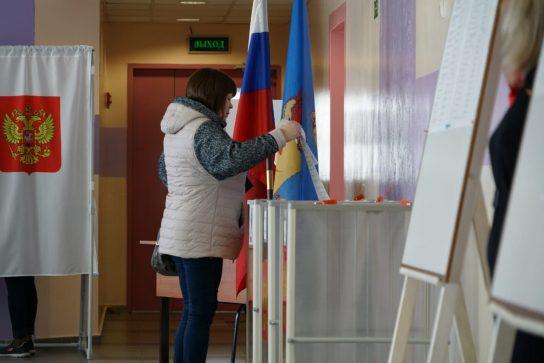 Женщина опускает бюллетень в урну на одном из избирательных участков Анадыря